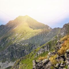 Fagaras Mountains from top view with sun spot. Blue sky with clouds on backgorund. Paltinu saddle, Romania