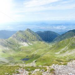Fagaras mountains from pathway in a cloudy day. Stream of water. Sky on background. Romania beauties