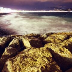 Sea shore and stones at night in Nice, France