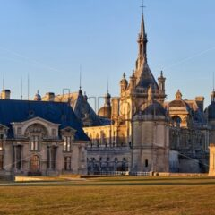 Chantilly Castle and Museum of Conde at sunset in France. Wide panoramic shot