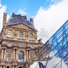 The Museum of Louvre during a cloudy day. The building is reflecting on the surface of a pyramid. Close up shot