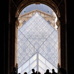 Vertical shot to people entering through the gates of Louvre. Symetric shot. Touristic locations in France
