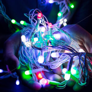 Boy holding Christmas lights in his hands. Holiday spirit idea. Vibrant colors. Shallow deph of field. Lots of colors