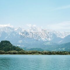 Lake Santa Croce at daylight. Mountains covered in snow on background. Province of Belluno, Veneto, northern Italy