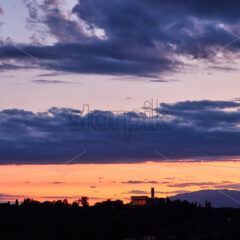 Sunset red sky with clouds above Conegliano city. Italy