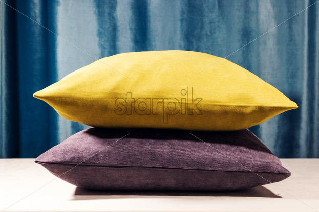 Yellow And Purple Pillows Standing One On To Another Blue Velvet Background Soft Light Coming From The Top Warm Whitebalance