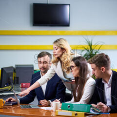 Team of caucasian mature women and men at meeting table discussing a business plan pointing at laptop computer in office