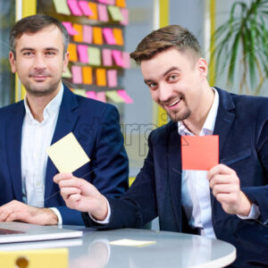 Two mature caucasian male having fun in the office with stickers. Wearing formal clothes.
