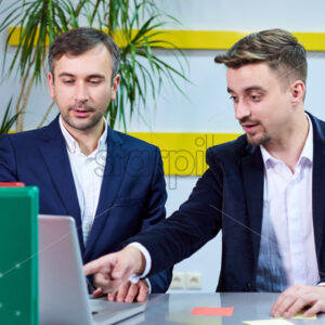 Two mature caucasian male working in the office, discussing a project on laptop. Wearing formal clothes