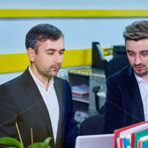 Two mature caucasian male working in the office, discussing a project on laptop. Wearing formal clothes. View through windo
