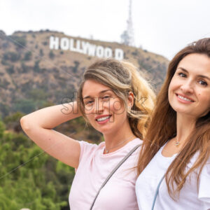 Happy blonde woman at the hollywood mountain in Los Angeles together with best friend, California - Starpik Stock