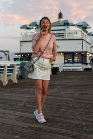 Happy blonde woman in pink sweater at the pier of Malibu, California - Starpik Stock