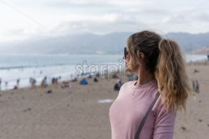 Happy blonde woman wearing sunglusses at the beach of Los Angeles, California - Starpik Stock