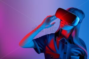 Woman with virtual reality set with blue and purple lights background - Starpik Stock