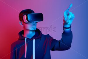 Young boy with virtual reality set with blue and purple lights background - Starpik Stock