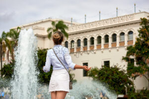 A caucasian woman spreading hands with fountain and building on the background in Balboa Park, San Diego - Starpik Stock