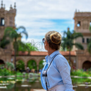 A caucasian woman turned away and looking on the aged building in Balboa Park, San Diego - Starpik Stock