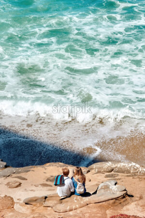 A couple sitting on the rocks near the Pacific ocean in San Diego, USA - Starpik Stock