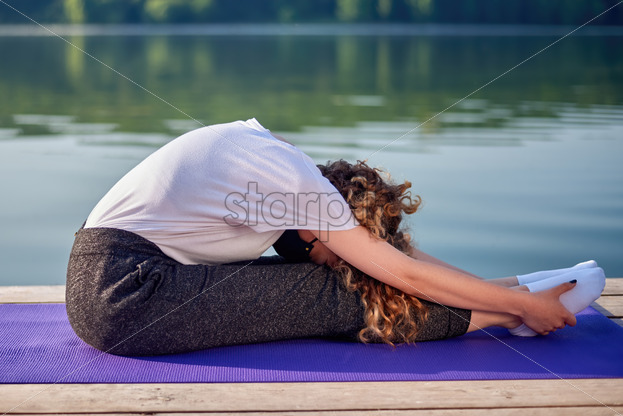 A young woman with curly hair and in medical mask doing yoga on a pier near a lake - Starpik Stock