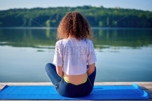 A young woman with curly hair doing yoga on a pier near a lake with green trees on the background - Starpik Stock
