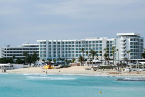 AYIA NAPA, CYPRUS – FEBRUARY 18, 2020: Vassos Nissi Plage Hotel with beach and blue water in front of it - Starpik Stock