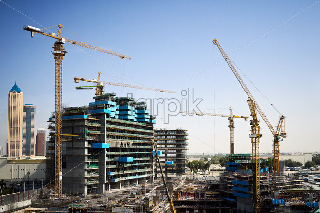 Construction site with cranes and people working. Dubai, United Arab Emirates - Starpik Stock