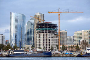 Construction works and high, modern buildings, yachts and two old moored boats on the foreground in San Diego, USA - Starpik Stock