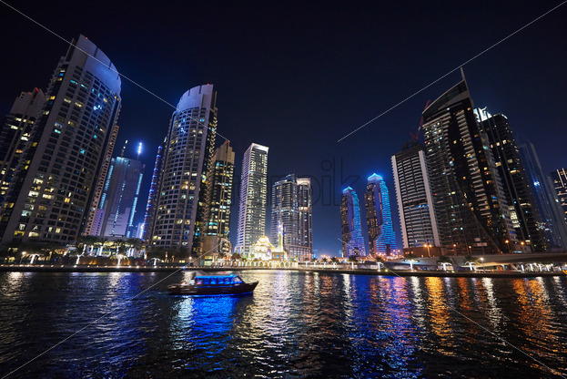 Dubai Marina at night with colorful touristic boats cruising on water. United Arab Emirates - Starpik Stock