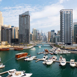 Dubai marina cityscape at daylight. Clear sky. United Arab Emirates. Yachts parked in port. - Starpik Stock