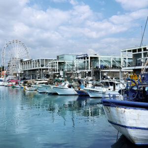 LIMASSOL, CYPRUS – FEBRUARY 17, 2020: Moored yachts in the wharf with cafes and Ferris ring on the background - Starpik Stock