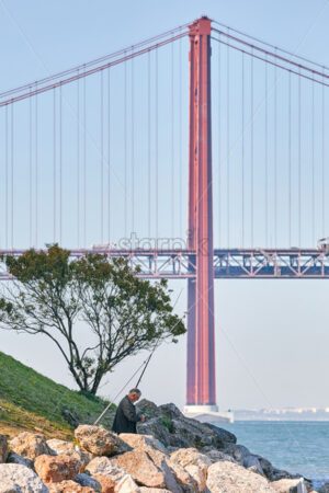 LISBON, PORTUGAL – OCTOBER 25 2019: Vertical shot of a fisherman occupied by a lovely deal and staying near the water with Ponte 25 de Abril bridge made of red metal in the background - Starpik Stock
