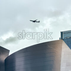 LOS ANGELES, USA – SEPTEMBER 26, 2019: High and modern buildings in downtown, flying plane in the distance - Starpik Stock