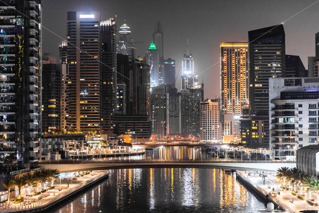 Modern looking view in Dubai at night, United Arab Emirates. Bright lights with orange predominance on the building - Starpik Stock