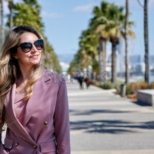 Portrait of a caucasian woman in sunglasses on embankment street in Limassol, Cyprus - Starpik Stock