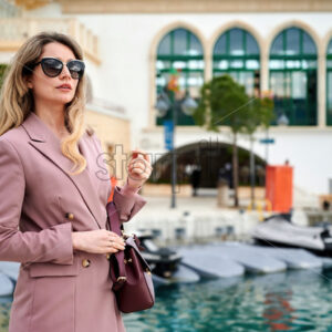 Portrait of a caucasian woman in sunglasses with bag and water channel on the background in Limassol, Cyprus - Starpik Stock