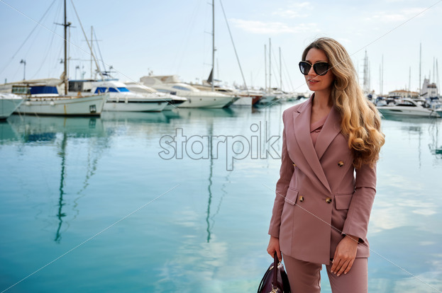 Portrait of a caucasian woman in sunglasses with bag and yachts on the background in Limassol, Cyprus - Starpik Stock