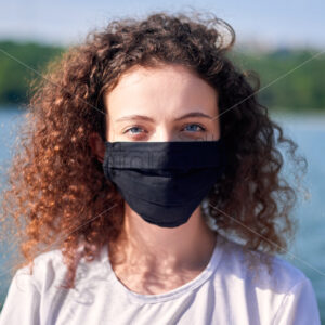 Portrait of a young woman with curly hair in medical mask near a lake with green trees on the background - Starpik Stock