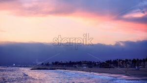 Santa Monica State beach at sunset, waves of the Pacific ocean, walking and relaxing people, Los Angeles, USA - Starpik Stock
