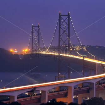 Shot of the huge Ponte 25 de Abril bridge in Lisbon Portugal taken at dusk towering above the chanel with multiple light tracks of many cars passing over it - Starpik Stock