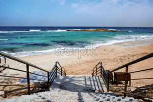 Stairs leading to the beach and blue, clear water in Ayia Napa - Starpik Stock