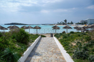 Trail leading to the sea and beach full of reed umbrellas in Ayia Napa - Starpik Stock