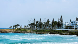 White residential buildings with palms and bubbling water on the foreground in Ayia Napa - Starpik Stock
