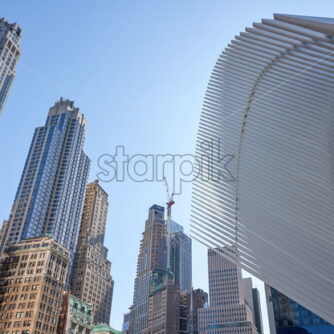 Wide shot of the World Trade Center station in New York with lots of high modern and aged buildings in the background. - Starpik Stock