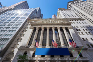 Wide shot of the grandiose New York Stock Exchange located at Wall Street, the sky behind the main scene is blue and clear - Starpik Stock