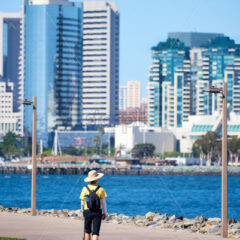 Woman with round classic hat walking the dog in waterfront park. San Diego, California - Starpik Stock