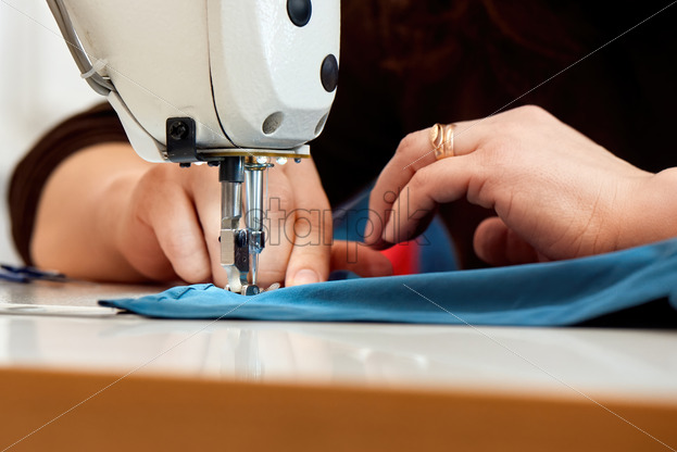 Woman working on a sewing machine with blue cloth - Starpik Stock