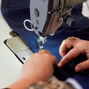 Woman working on a sewing machine. Blue cloth - Starpik Stock