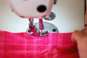 Woman working on a sewing machine. Red cloth - Starpik Stock