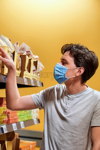 Young man with a protective medical mask looking at the snacks from the shelves in a supermarket. Corona Virus idea - Starpik Stock
