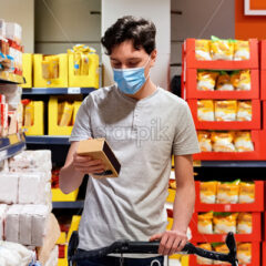 Young man with a protective medical mask looking at the sugar near the cart in supermarket. Corona Virus idea - Starpik Stock